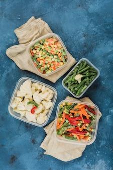 Warzywa mrożone: mieszanka warzyw, fasoli szparagowej i kalafiora w różnych plastikowych pojemnikach do zamrażania z serwetkami na niebieskim tle.