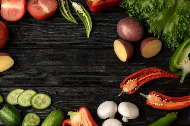 Warzywa na czarnym drewnianym stole, widok z góry i miejsce na kopię w środku