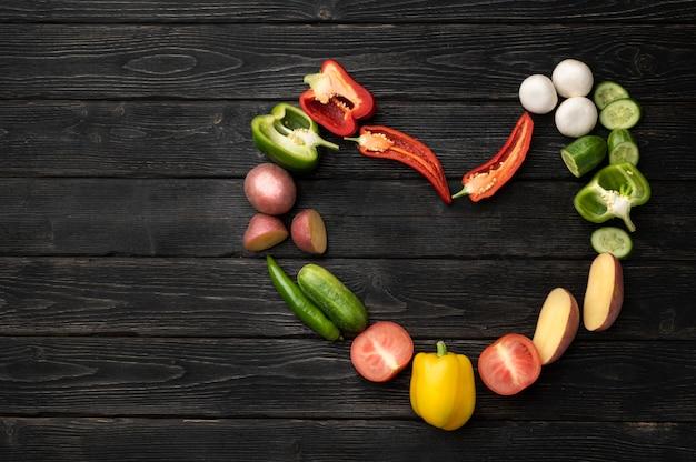 Warzywa na czarnym drewnianym stole. widok z góry z miejscem na kopię