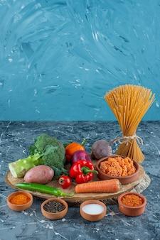 Warzywa na desce obok makaronu spaghetti na marmurowej powierzchni