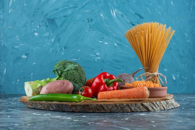 Warzywa na desce obok makaronu spaghetti, na marmurowym tle.