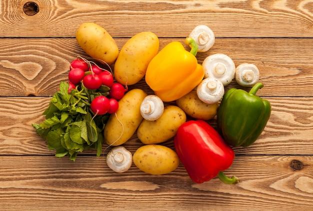 Warzywa na drewnianym tle. ziemniaki, pieczarki, papryka, rzodkiew