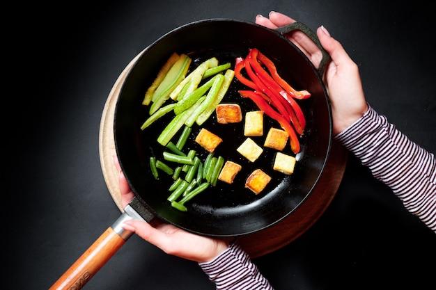 Warzywa na patelni są smażone. czarne tło.