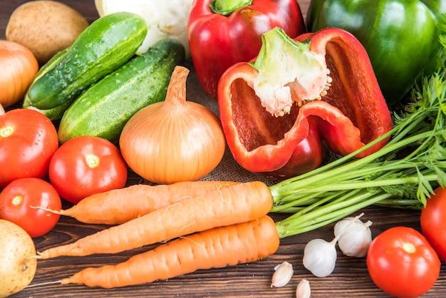 Warzywa na podłoże drewniane. marchew, papryka czerwona, ogórki, pomidory, czosnek, ziemniaki i cebula.