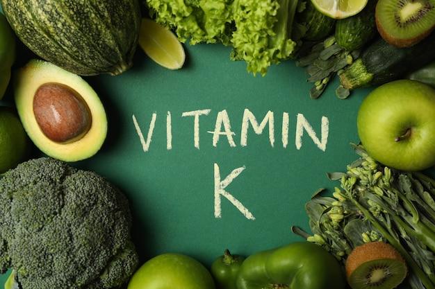 Warzywa, owoce i tekst witamina k na zielonym tle