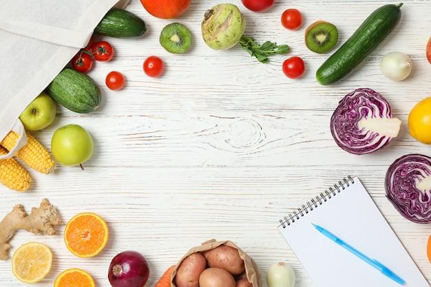 Warzywa, owoce, torba z materiału i zeszyt z długopisem na drewnie