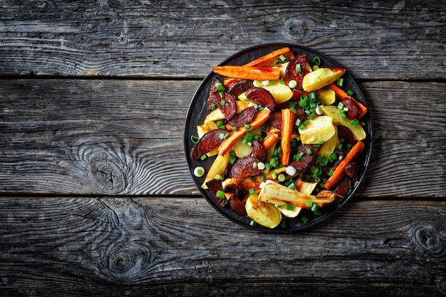 Warzywa pieczone w piekarniku, burak krojony, łódeczki ziemniaczane, pasternak, marchew posypane posiekaną zieloną cebulą na czarnym talerzu na drewnianym stole, widok poziomy z góry, ułożenie na płasko, wolna przestrzeń
