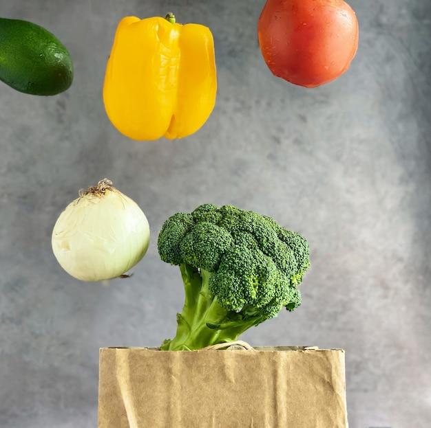 Warzywa pomidor, papryka, cebula, brokuły lewitujące nad papierową torbą na zakupy. koncepcja zdrowego stylu życia i żywienia.