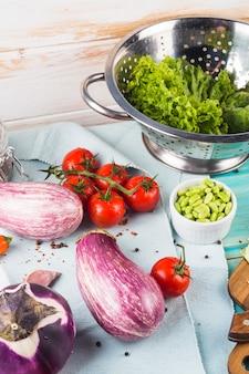 Warzywa; przyprawy i sitko na obrusie nad drewnianym stołem