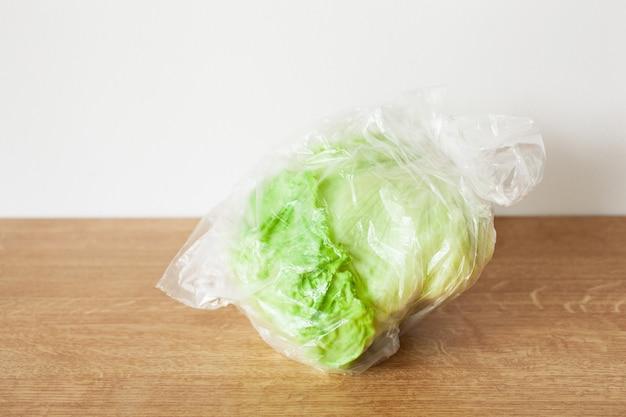 Warzywa sałaty lodowej w plastikowej torbie. problem z plastikowym opakowaniem jednorazowego użytku
