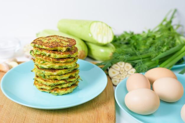 Warzywa smażone naleśniki z cukinią i zieleniną na niebieskim talerzu na jasnym tle na drewnianej desce. widok z góry, selektywne ustawianie ostrości, miejsce na tekst