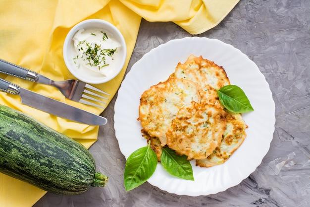 Warzywa smażone placki z cukinii i liści bazylii na talerzu i sos śmietanowy z zieleniną w misce na stole. widok z góry