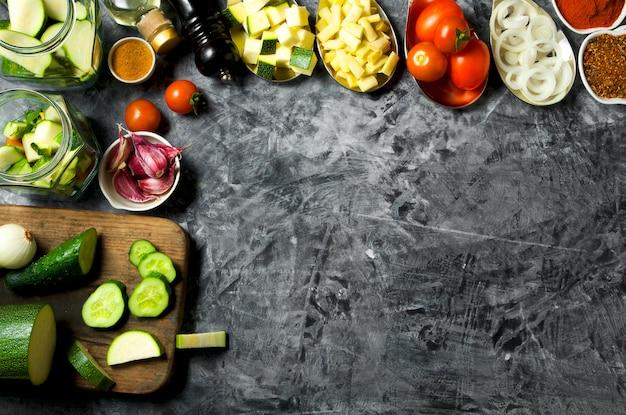Warzywa . świeże warzywa (ogórki, pomidory, cebula, czosnek, koperek, fasolka szparagowa) na szarym tle. widok z góry. copyspace