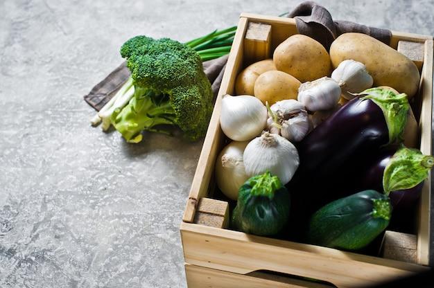 Warzywa w drewnianym pudełku: ziemniaki, cebula, czosnek, bakłażan, cukinia, brokuły, zielona cebula.