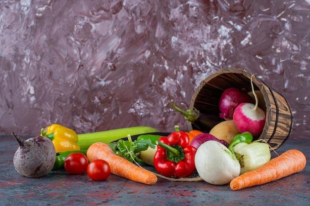 Warzywa w przewróconym wiadrze, na marmurowym tle.