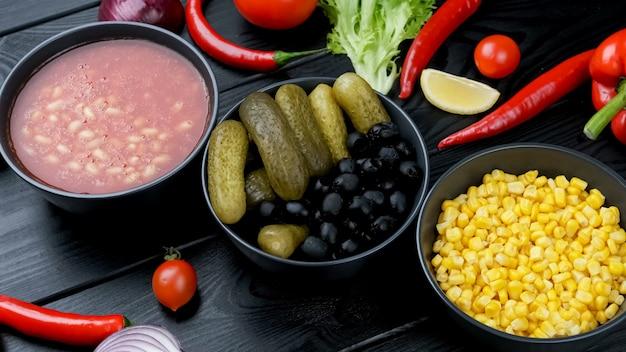 Warzywa w puszkach w talerzu. ogórek, kukurydza, fasola. na czarnej tablicy