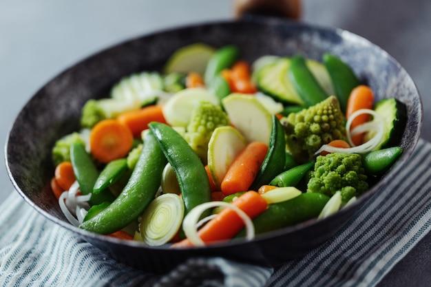 Warzywa wegańskie smażone na patelni lub gotowe do gotowania na stole. zbliżenie. selektywne skupienie