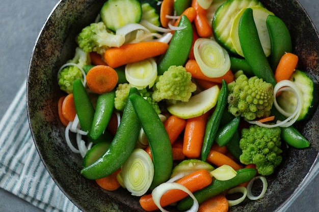 Warzywa wegańskie smażone na patelni lub gotowe do gotowania na stole