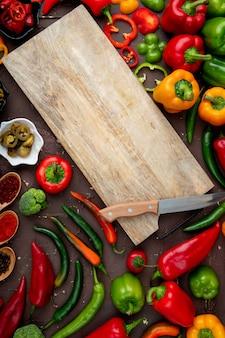 Warzywa z deską do krojenia na bordowym stole