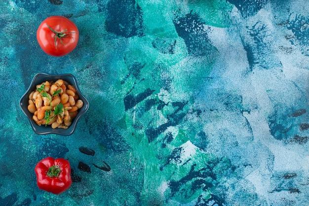Warzywa z miską fasolki po bretońsku, na niebieskim stole.