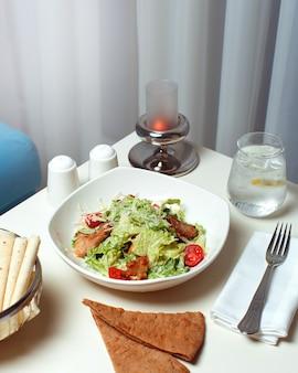 Warzywa z przodu gotowane na białej płytce wraz z plastry i kromki chleba na białym stole