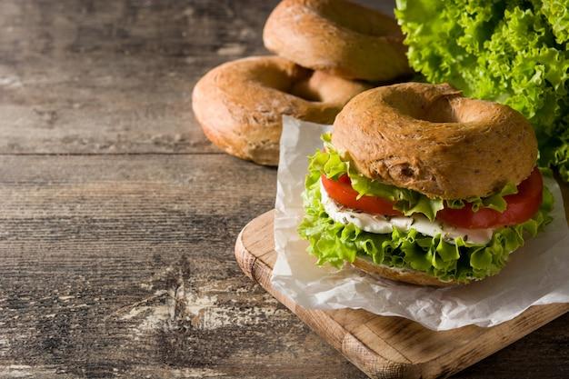 Warzywna bajgiel kanapka z pomidorem, sałatą i mozzarellą na drewnianym stole kopii przestrzeni