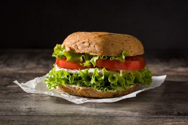 Warzywna bajgielowa kanapka z pomidorem, sałatą i mozzarellą na drewnianym stole.