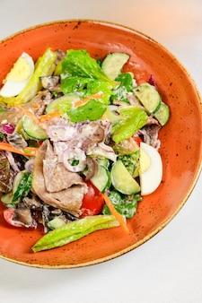 Warzywna sałatka wegetariańska z pomidorami, papryką i cebulą na białym stole. zdrowa sałatka ze świeżych dojrzałych letnich warzyw