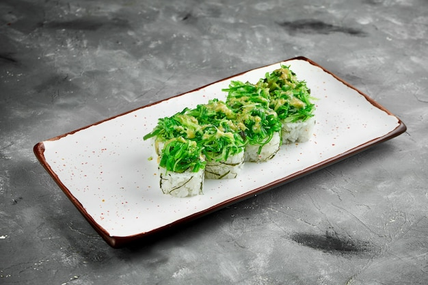 Warzywne roladki sushi z wodorostami hiyashi i sosem orzechowym na białym talerzu na szarym stole. japońskie jedzenie