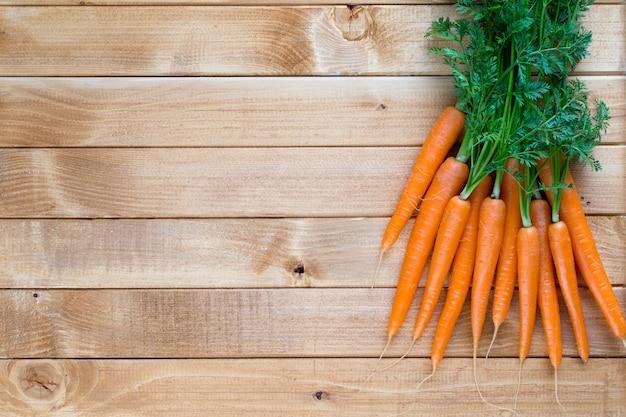 Warzywo świeże marchewki z liśćmi na podłoże drewniane.