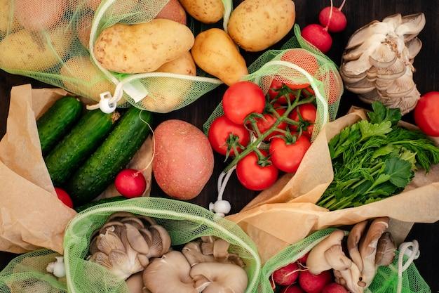 Warzywo w wielokrotnego użytku torbach na drewnianym tle, odgórny widok