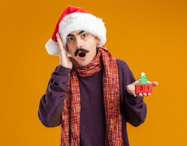 Wąsaty mężczyzna w czapce świętego mikołaja z ciepłym szalikiem na szyi, trzymający kostki zabawek z datą noworoczną zdumiony i zaskoczony, stojąc nad pomarańczową ścianą