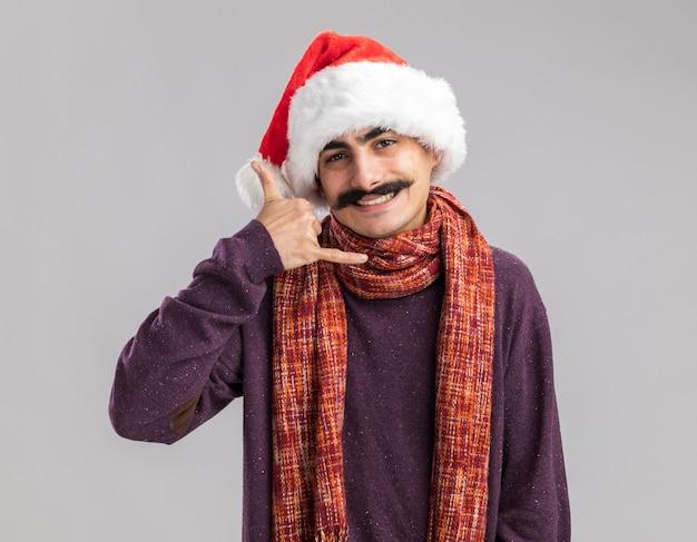 """Wąsaty mężczyzna w czapce świętego mikołaja z ciepłym szalikiem na szyi z uśmiechem na twarzy wykonującym gest """"zadzwoń do mnie"""" stojący nad białą ścianą"""