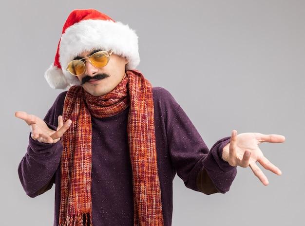 Wąsaty mężczyzna w świątecznym czapce mikołaja i żółtych okularach z ciepłym szalikiem na szyi patrząc na kamerę zdezorientowany z wyciągniętymi rękami stojąc na białym tle