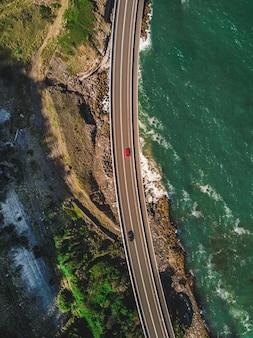 Wąska kręta droga z samochodami wzdłuż zielonych gór