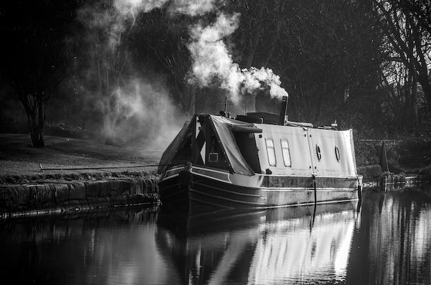 Wąska łódź w rzece, w liverpoolu, wielka brytania. czarny i biały