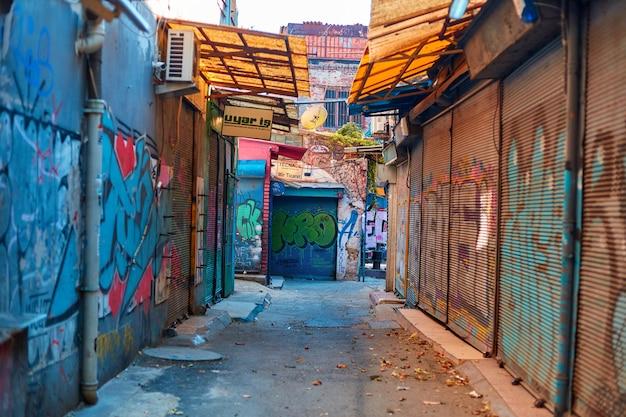Wąska ulica targowa pokryta graffiti
