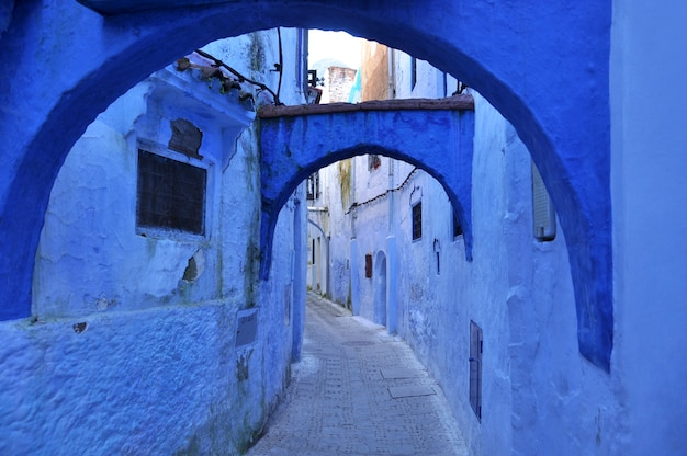 Wąska ulica z niebieskimi ścianami i łukami w marokańskim mieście chefchaouen
