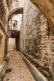 Wąska uliczka pokryta kamiennymi łukami na starym mieście w awinionie