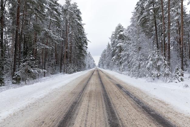 Wąska zaśnieżona zimowa droga dla ruchu samochodowego, zachmurzone niebo na jezdni, śnieg na jezdni topi się od ruchu samochodowego