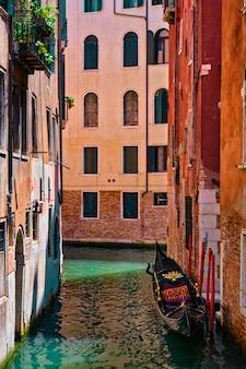 Wąski kanał między kolorowymi starymi domami z gondolą w wenecji, włochy