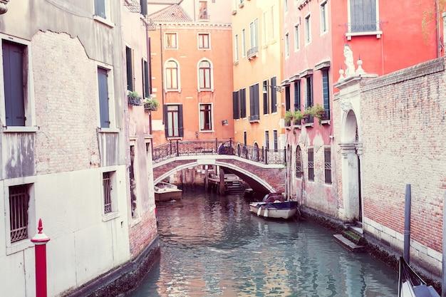 Wąski kanał z mostem i kolorową architekturą w wenecji