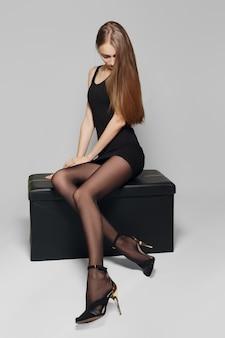 Wąski model w krótkiej czarnej sukience i długich nogawkach w rajstopach na skórzanym pudełku.