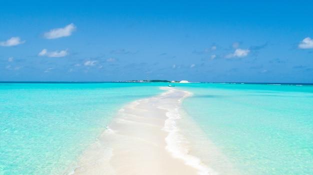 Wąski wierzchołek wyspy pokrytej czystym piaskiem z obu stron czystą wodą