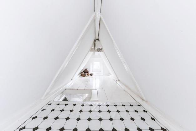 Wąskie pomieszczenie na poddaszu ze ścianami ze stożkowego dachu zdobionego dachówką i białą farbą