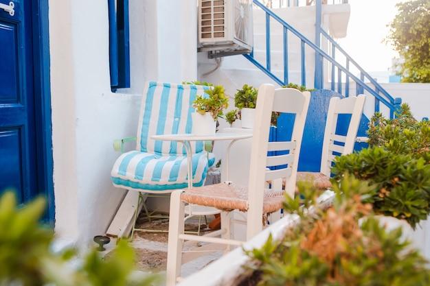 Wąskie uliczki wyspy z niebieskimi balkonami, schodami i kwiatami. piękny taras z zewnątrz w stylu cykladzkim.