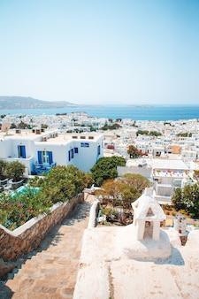 Wąskie uliczki wyspy z niebieskimi balkonami, schodami i kwiatami w grecji.