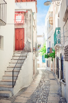 Wąskie uliczki wyspy z niebieskimi balkonami, schodami i kwiatami.