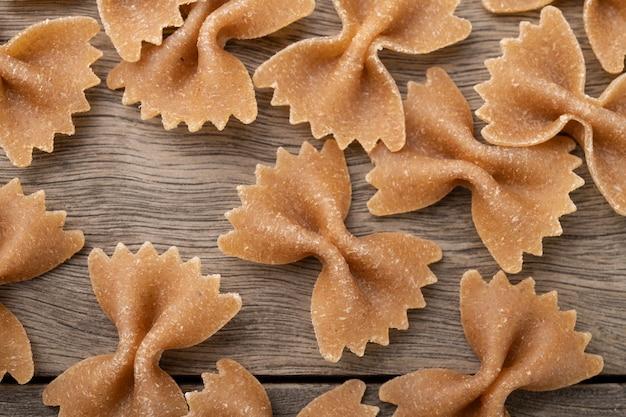 Wąskie zbliżenie ostrości makaronu farfalle pełnoziarnistego na drewnianym stole.
