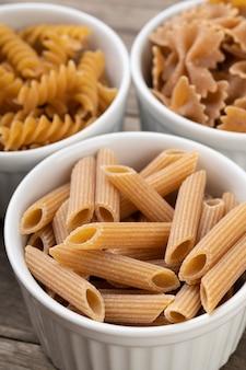 Wąskie zbliżenie ostrości wybrane makarony pełnoziarniste na miski.